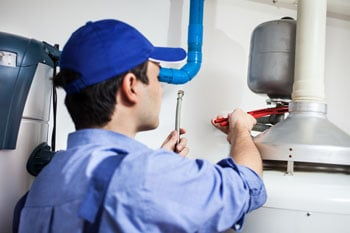 plumber with blue hat repairing old tank hot water system in wollongong